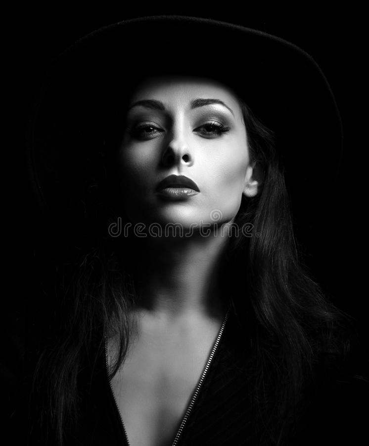 Glamour makeup woman posing in fashion hat on dark backgrou stock photography