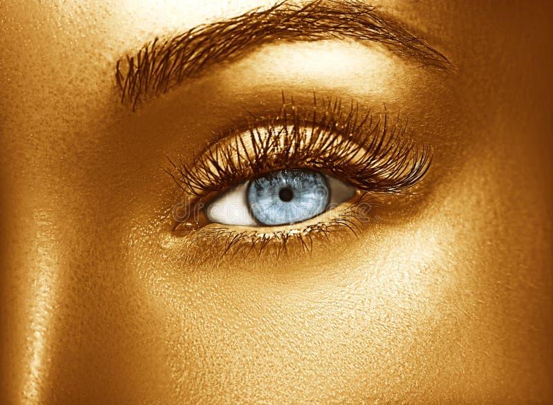 Glamour shiny gold professional makeup. Beautiful golden skin close up. stock photography