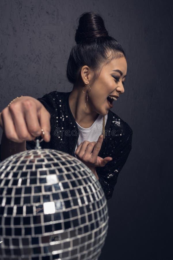 glamour vrolijk Aziatisch meisje met gekomen hier de discobal van de gebaarholding royalty-vrije stock foto's