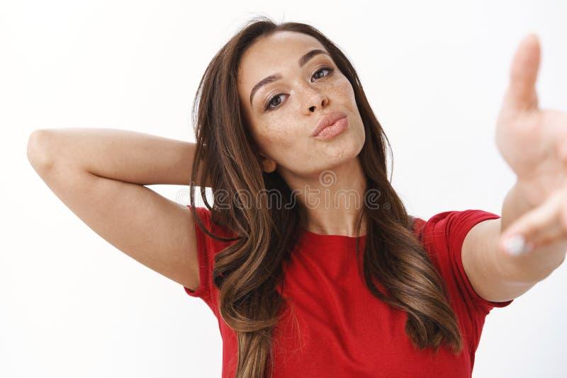 Glamour, vrouwen en levensstijl Sassy brunette vrouwtje met freckles in rood T-shirt, breid arm uit stock fotografie