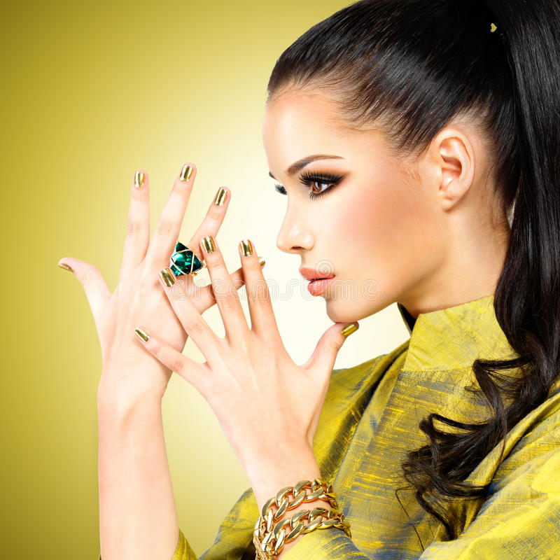 Glamour woman with beautiful golden nails and emerald ring stock photo