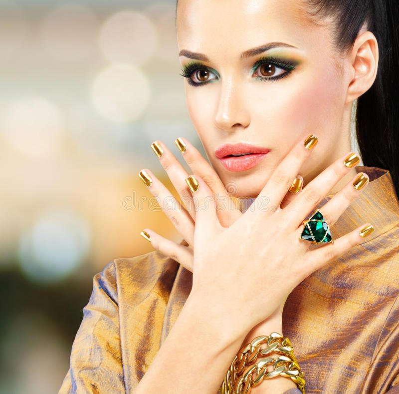 Glamour woman with beautiful golden nails and emerald ring royalty free stock photo