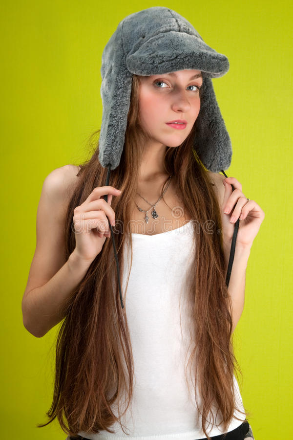 Glamour woman and fur-cap. On green background royalty free stock image