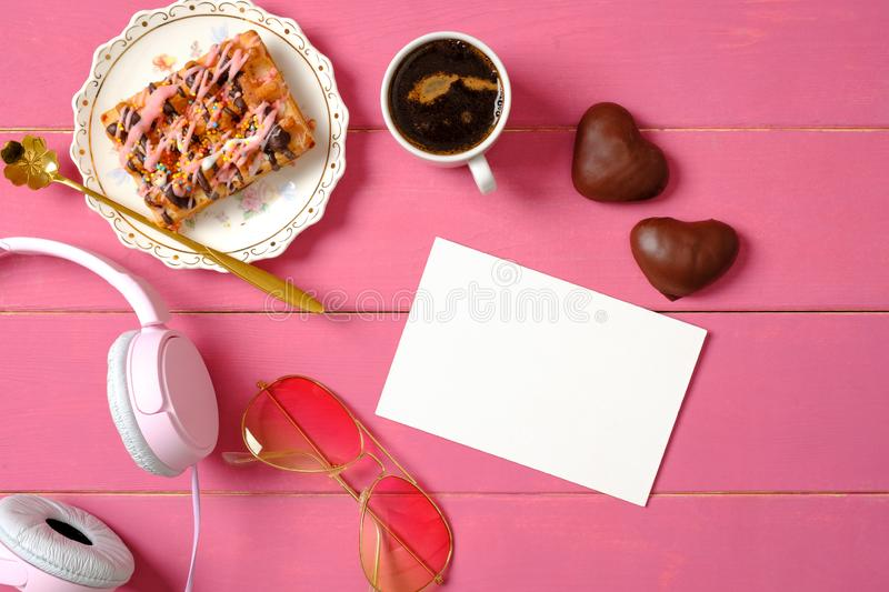Glamour women desk with beauty blogger accessories and tasty food: headphones, glasses, cup of coffee, heart-shaped chocolate, stock photography