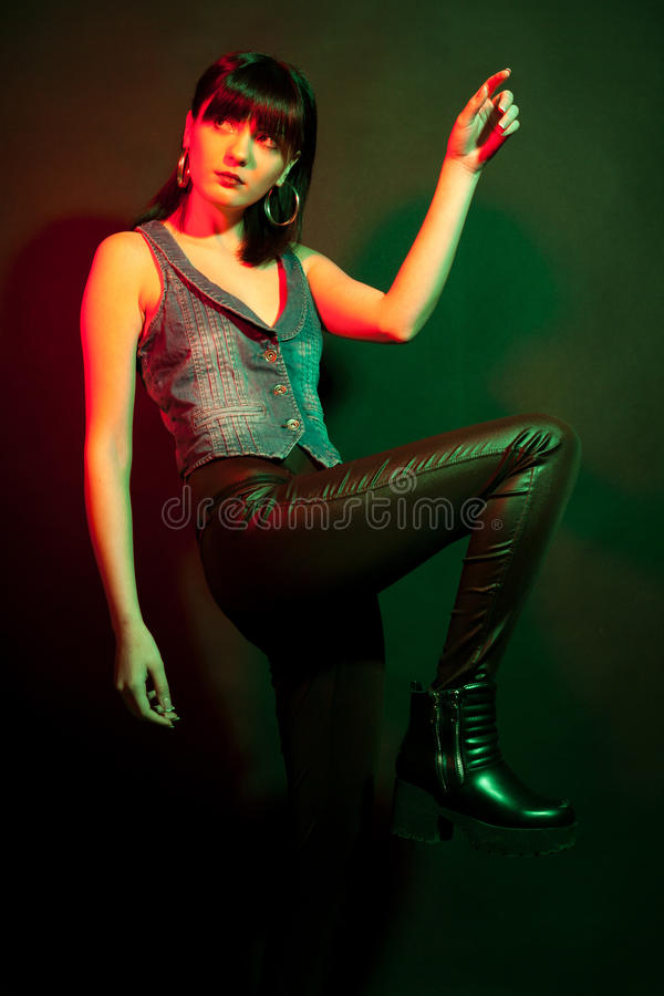 Glamourbrunetten i läder flåsar i rött och klartecken fotografering för bildbyråer
