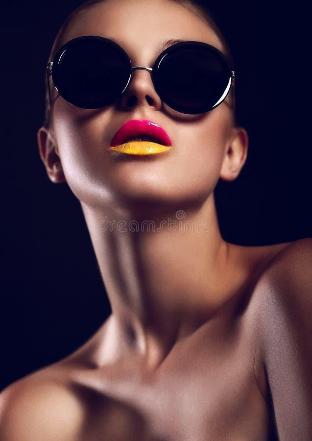 Glamourcloseupstående av det härliga sexiga stilfulla funktionsläget i solexponeringsglas med ljusa färgrika kanter med perfekt re royaltyfri foto