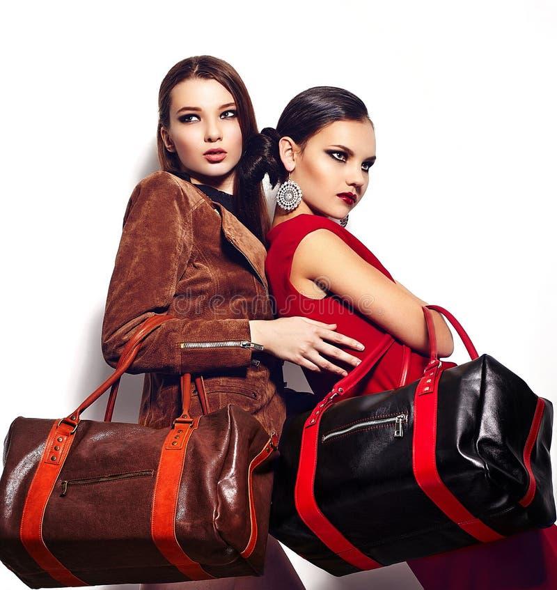 Glamourcloseupståenden av två Caucasian unga kvinnor för härliga sexiga stilfulla brunetter modellerar med ljus makeup, med röda k arkivfoton