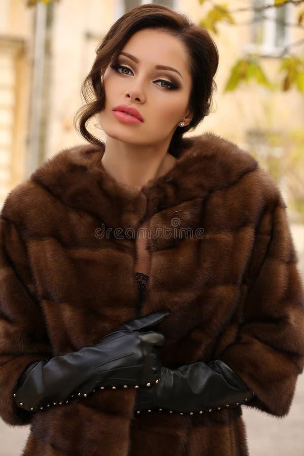 Glamourkvinna med mörkt hår som bär det lyxiga pälslaget arkivbilder