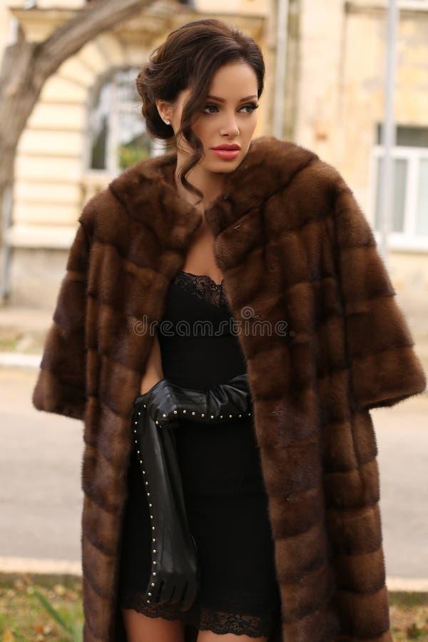 Glamourkvinna med mörkt hår som bär det lyxiga pälslaget royaltyfri foto