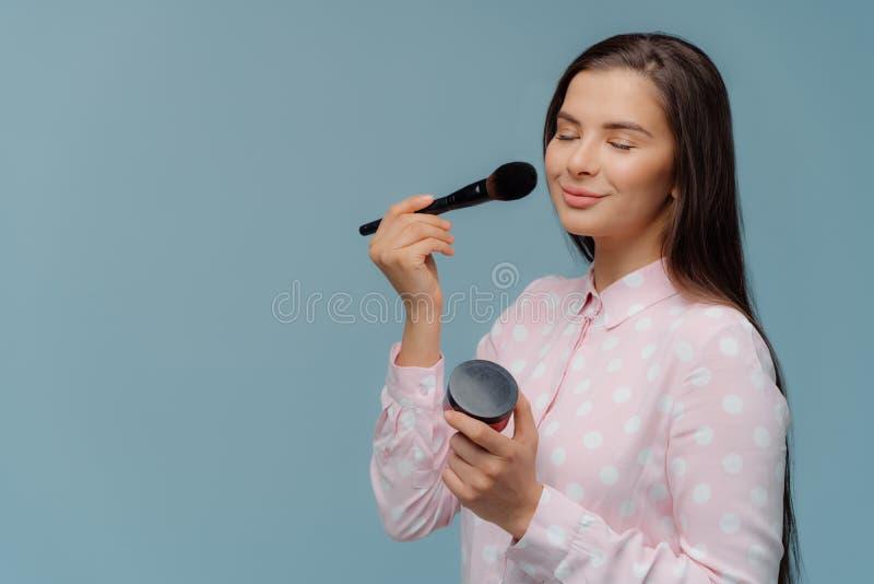 Glamourkvinnan applicerar rodnad med makeupborsten, gör henne som egna utgör, omsorger om framsidahud, uppehällen ögon stänger, i royaltyfri bild
