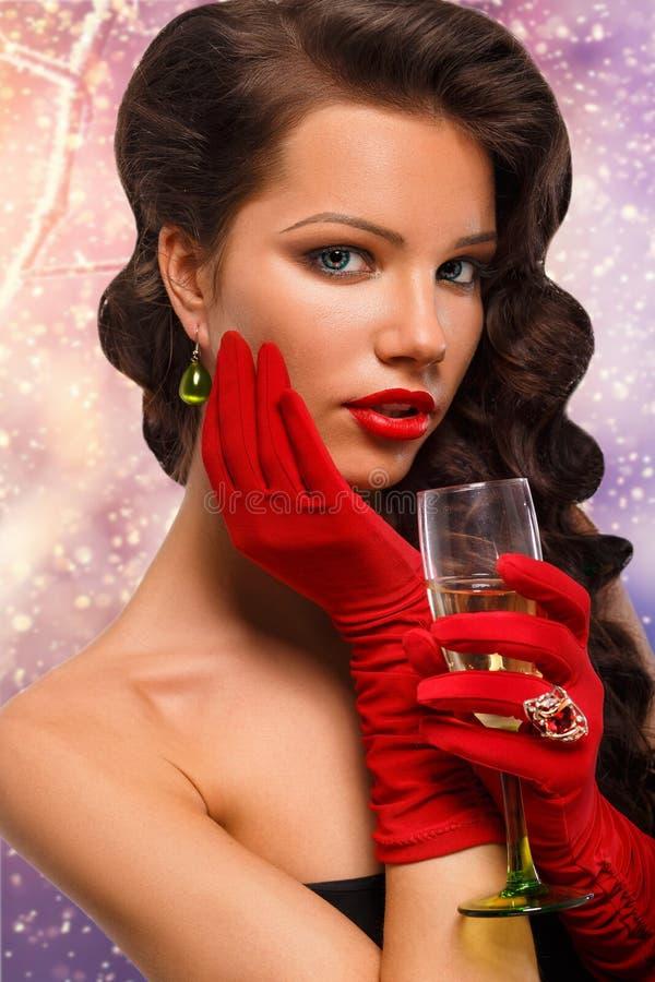 Glamourmeisje die in rode handschoenen een glas champagne houden Het drinken Champagne Schoonheidsvrouw met perfecte maniermake-u royalty-vrije stock fotografie