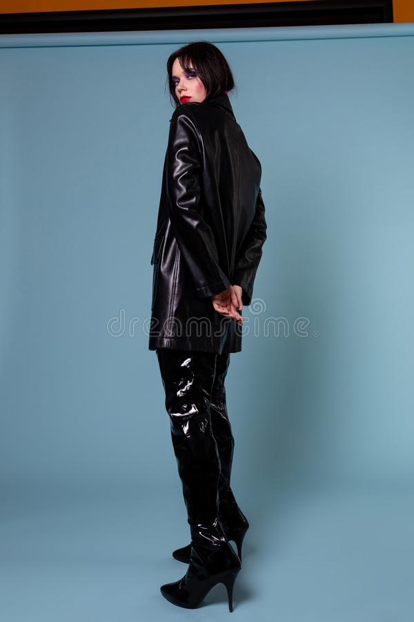 Glamourmodell med mörkt kort hår i svartläderomslag i storformat royaltyfri bild