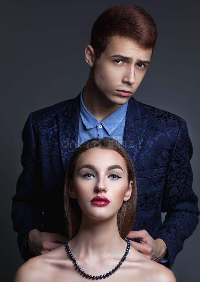 Glamourmodepar Mannen för den unga mannen sätter på en perl-halsband på royaltyfri fotografi
