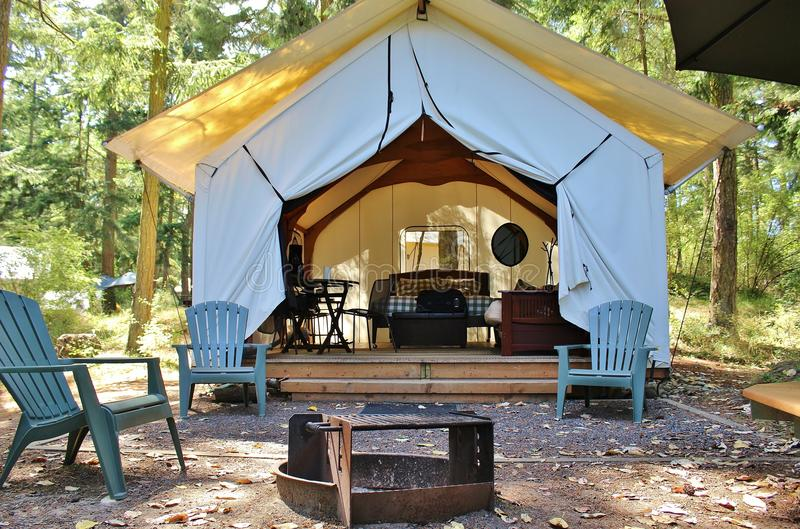 Glamping cabin in the woods. Campsite with canvas tent fully furnished glamping cabin, fire pit, and picnic area in the forest royalty free stock photos