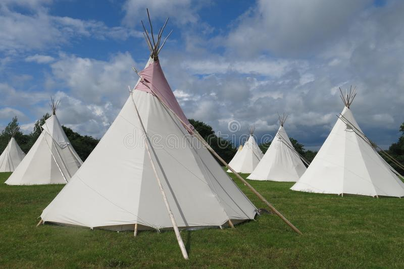Glamping camping tipis tepees. In a field on sunny day royalty free stock photos
