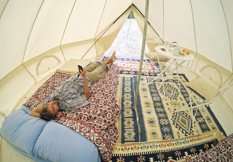 Glamping outdoor accomodation. Tourist men with smartphone lying on bed inside camping tent with cozy interior royalty free stock photography