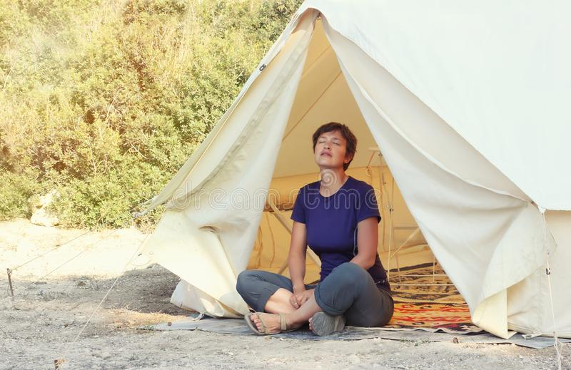 Glamping outdoor vacation. Woman relax near big camping tent with cozy interior. Luxury travel accomodation into the forest royalty free stock photo