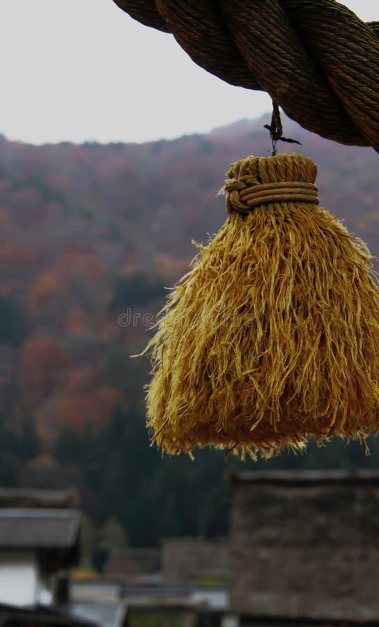 Gland de paille accroché de la corde de paille de riz de Shimenawa dans le village de Shirakawago image stock
