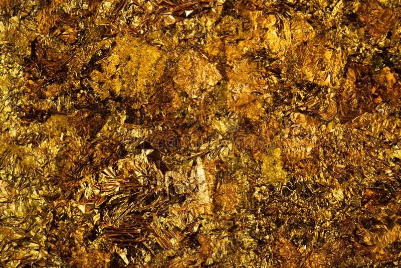 Glanzend geel bladgoud of schroot van gouden folietextuur als achtergrond stock afbeeldingen