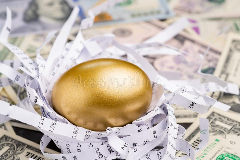 Glanzend gouden ei in document nest met financiële aantallen op stapel van het geldmetafoor van het Amerikaanse dollarbankbiljet  stock foto