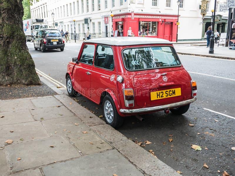 Glanzend rood Mini Cooper op de straat van Londen stock foto