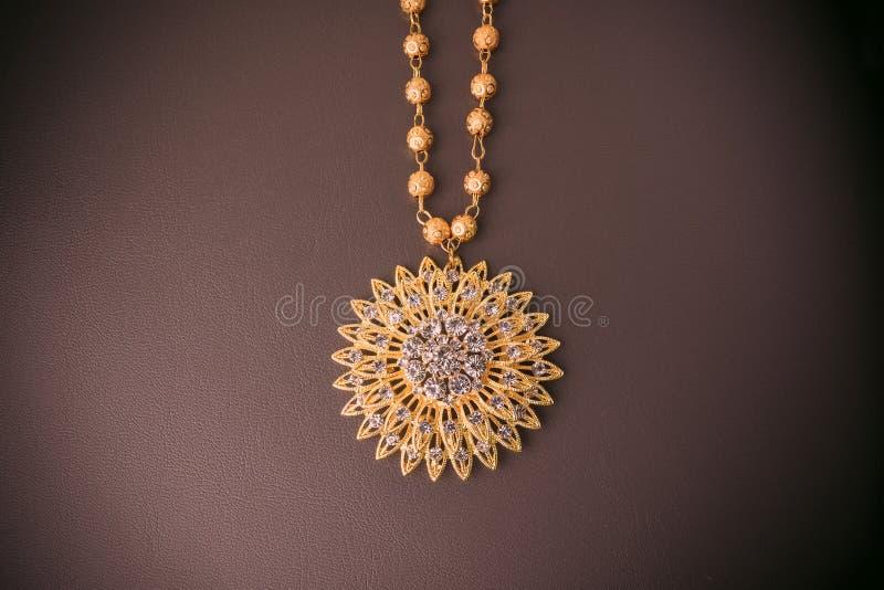 glanzende gouden juwelen op Bruin leer stock afbeelding