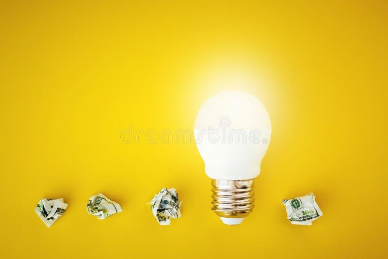 Glanzende lamp en verfrommelde document dollarrekeningen op gele achtergrond stock foto