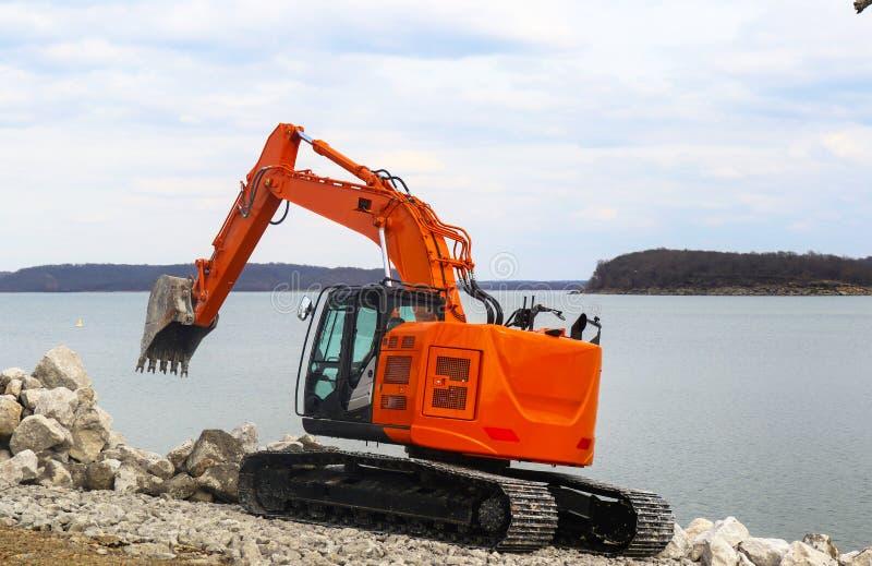 Glanzende nieuwe oranje backhoe op sporen door meer die grote keien schikken door het water royalty-vrije stock foto