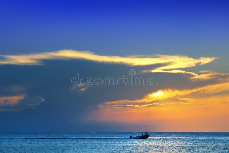 glanzende overzees en motorboot over bewolkte hemel en zon tijdens zonsondergang in Cozumel, Mexico stock foto's