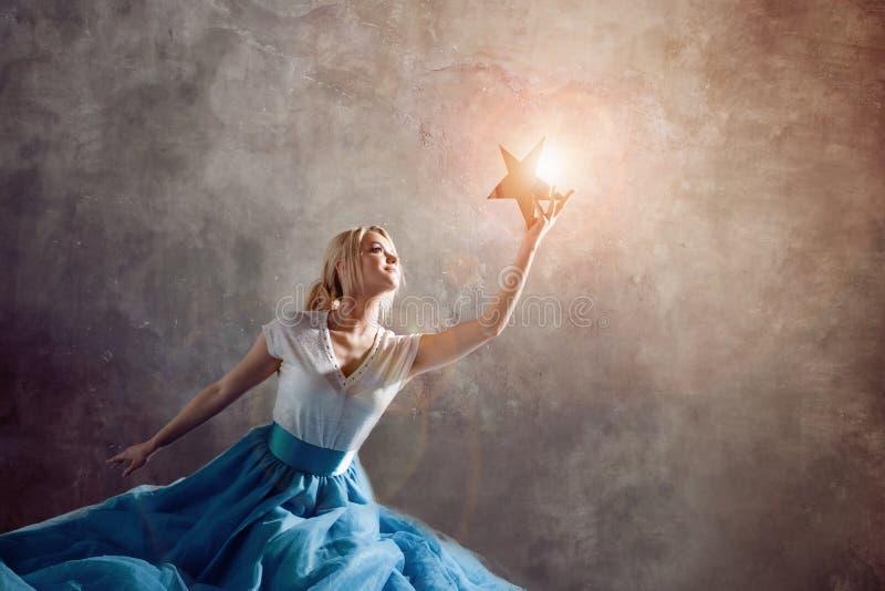 Glanzende ster ter beschikking, bereik voor het droomconcept Jonge vrouw die een ster in haar hand houden royalty-vrije stock afbeelding