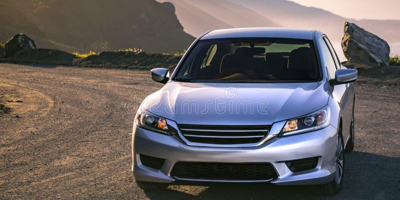 Glanzende zilveren die auto op een zonnige bergweg wordt geparkeerd royalty-vrije stock afbeelding