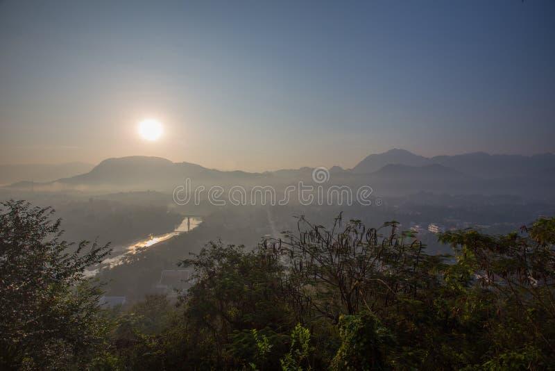 Glaring sunrise over Luang Prabang mountains, river stock photo