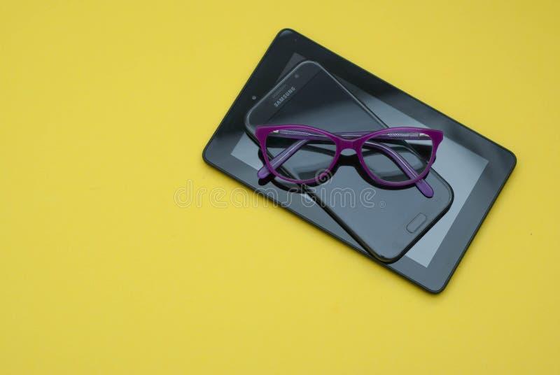 Glasögon över minnestavlan och mobiltelefonen över gul bakgrund med kopieringsutrymme Utbildning technoogy, internet arkivbilder
