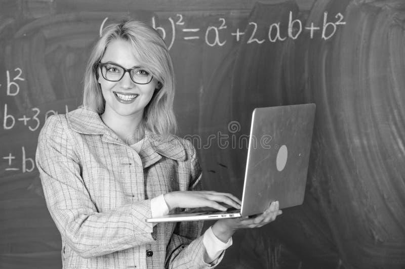 Glasögon för kvinnalärarekläder rymmer bärbara datorn som surfar internet Smart klyftig dam för utbildare med modernt bärbar dato royaltyfria bilder