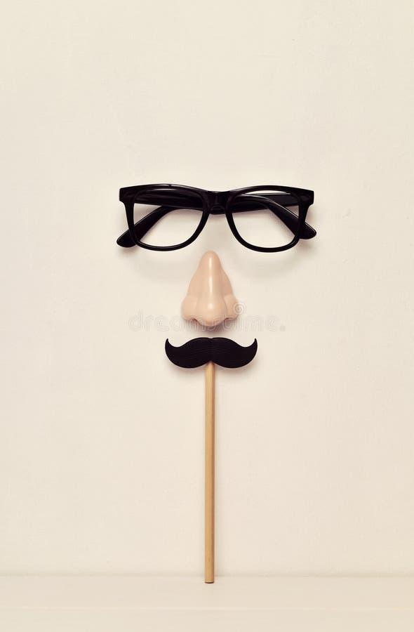 Glasögon, näsan och mustaschen som visar en man, vänder mot royaltyfria foton