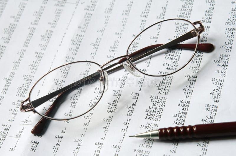 Glasögon och blyertspenna på dokument royaltyfri foto