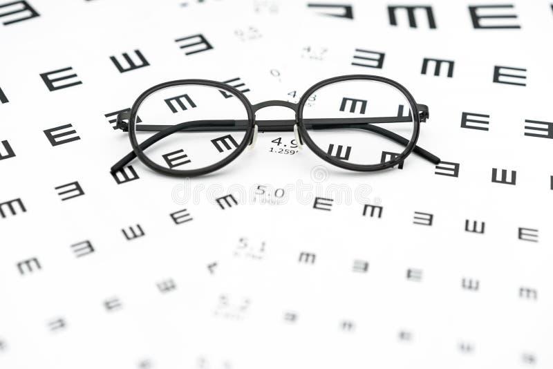 Glasögon och diagram för visuell skärpa i vit bakgrund arkivbilder