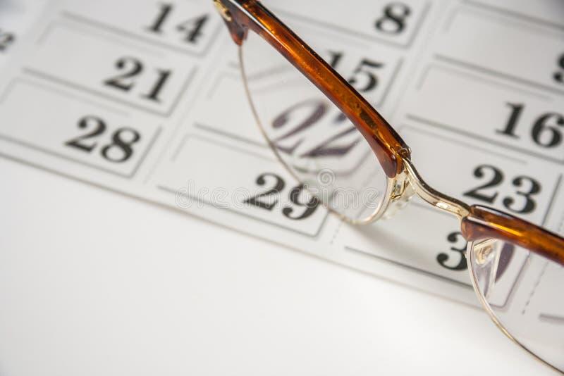 Glasögon och kalendern royaltyfria foton