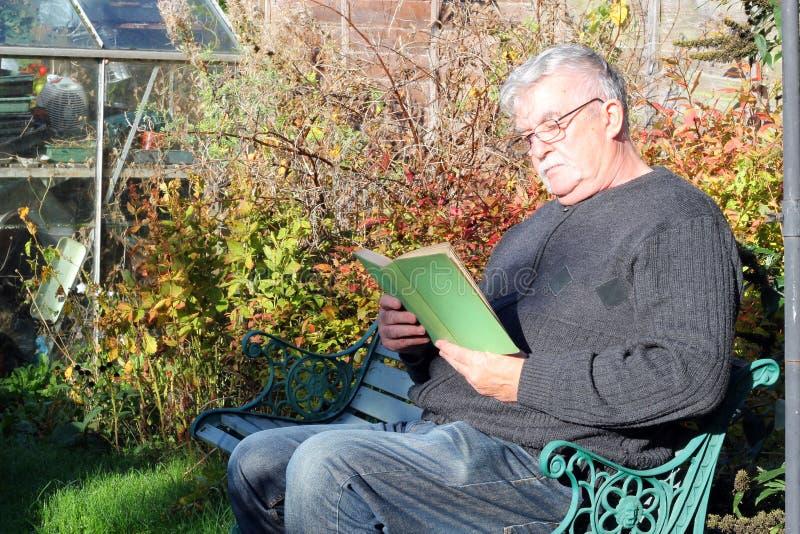 Glasögon och läsning för äldre man bärande en bok royaltyfria bilder