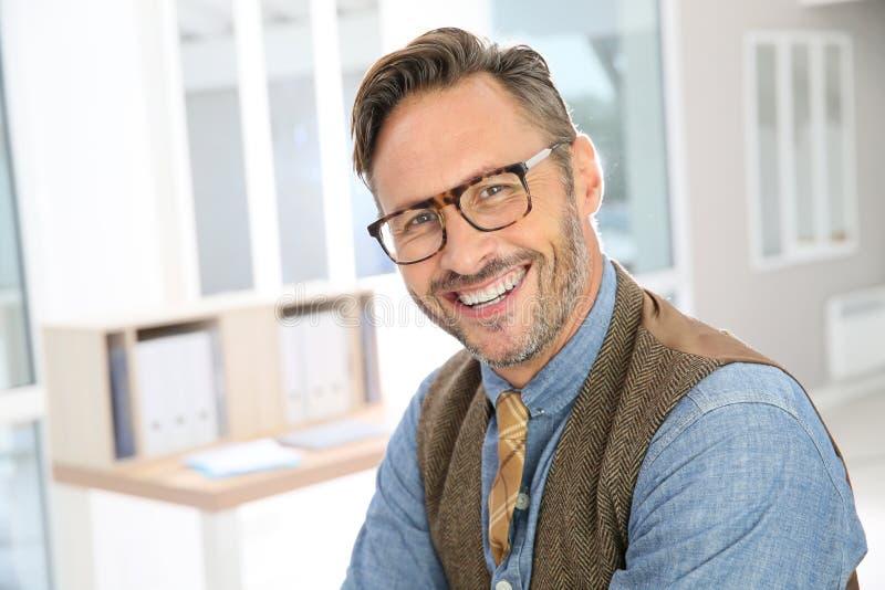 Glasögon och le för stilig stilfull man bärande arkivbild