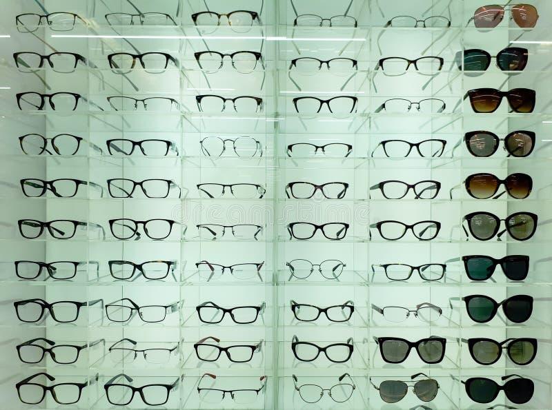 Glasögon och solglasögon på hyllor royaltyfri foto