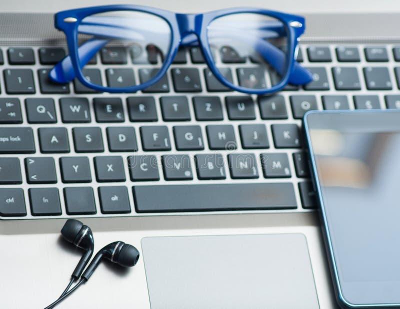 Glasögon på bärbar datortangentbordet med smartphone- och hörlurarkontorsconceptEyeglasses på bärbar datortangentbordet med smart arkivfoton