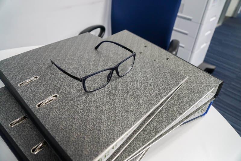 Glasögon på högen av affärsmappar för granskning royaltyfri bild
