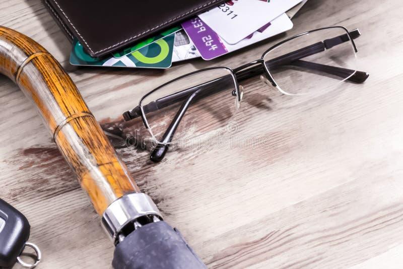 Glasögon, paraply, bilnyckel, kreditkort i läderplånbok på träbord arkivfoton