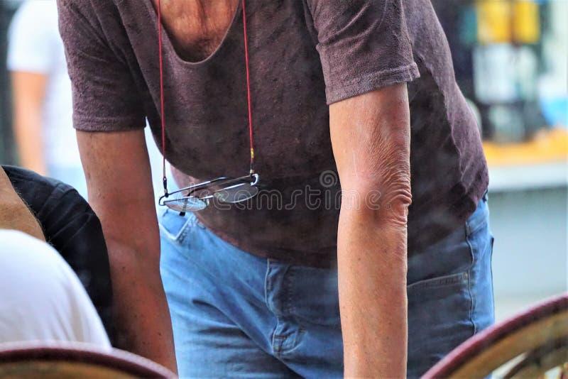 Glasögon som hänger på röda sladd runt halsen på äldre personer arkivfoton
