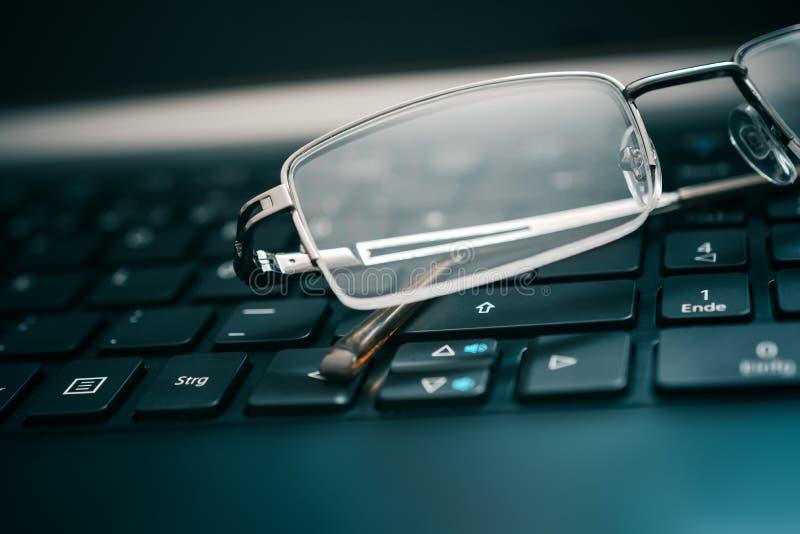 Glasögon som ligger på det mörka datortangentbordet royaltyfria foton