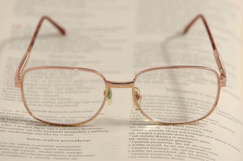 Glasögon som ligger på en gammal bok royaltyfri foto