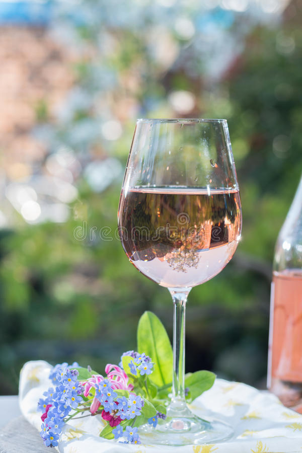 Glas του κρύου ροδαλού κρασιού, υπαίθριο terrase, ηλιόλουστη ημέρα, άνοιξη garde στοκ φωτογραφία με δικαίωμα ελεύθερης χρήσης