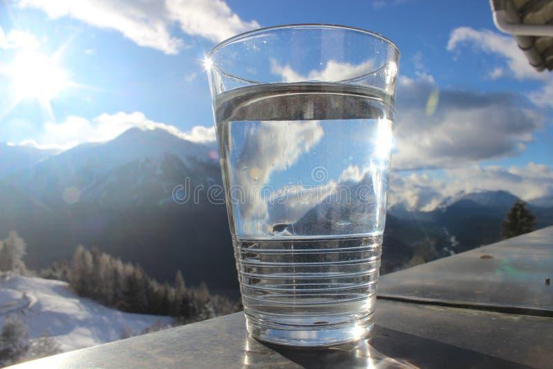 Glas минеральной воды на перилах с ландшафтом горы и голубым облачным небом стоковое фото