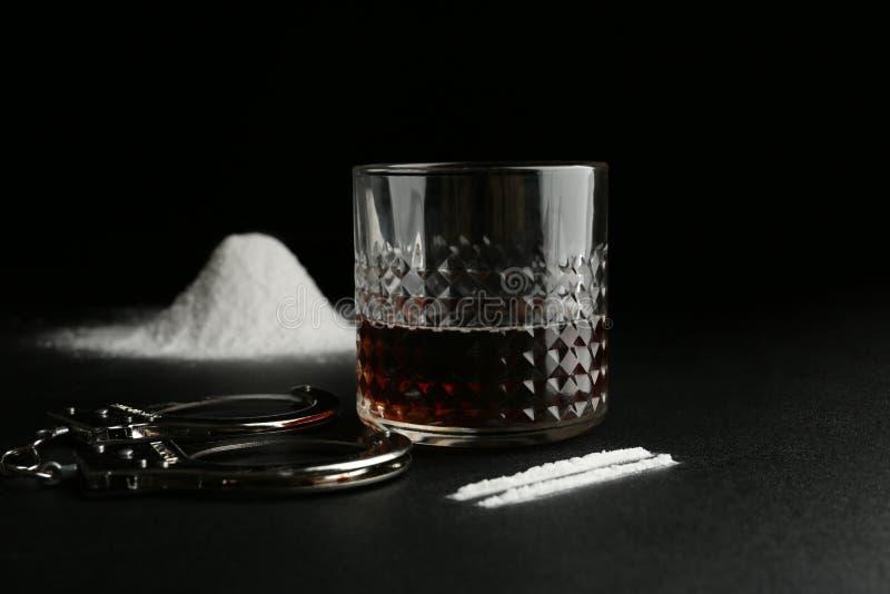 Glas Alkohol, Kokain und Handschellen lizenzfreie stockfotos